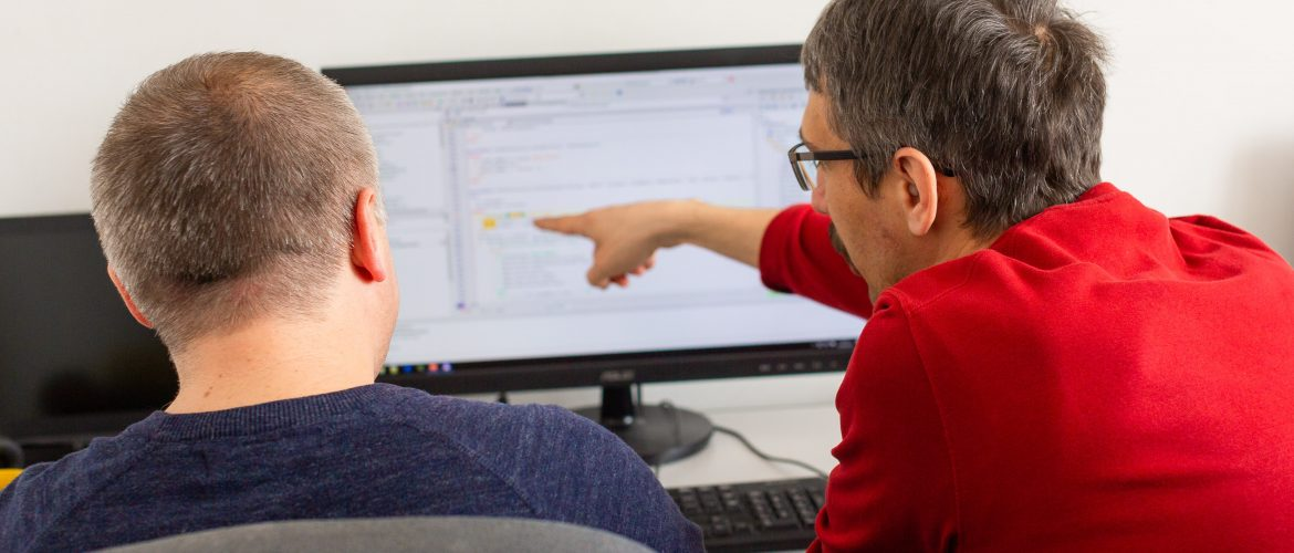 two software developers discussing in front of a monitor
